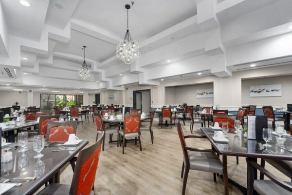 Main dining room with light wood floors ad arange back arm chairs