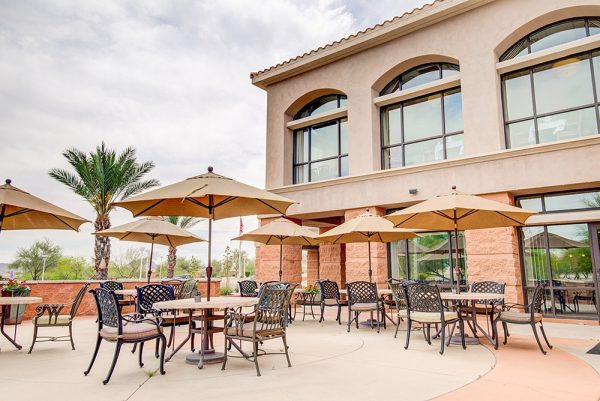 Fountain View Village community patio with many umbrella tables for residents to sit