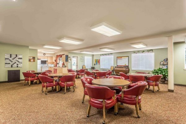 Apple Blossom activity room with many four top tables and red leather chairs