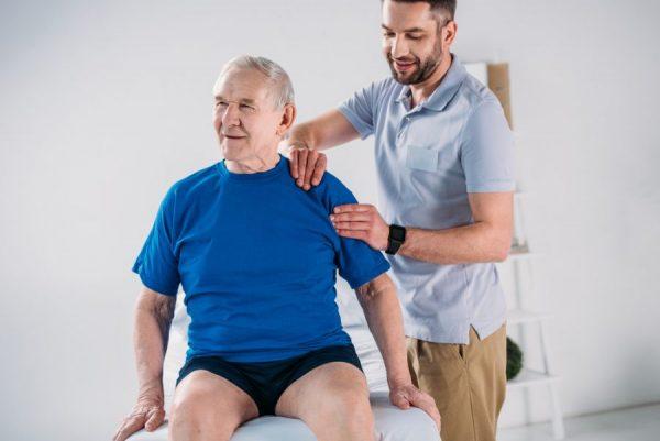 Male Sapphire of Tucson Nursing and Rehab caregiver massaging shoulder of senior man