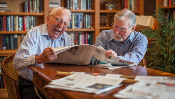Two senior men lauging while reading the newspaper in The Terrace at Priceville