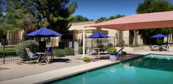 Outdoor swimming pool and umbrella tables at North Chandler Place