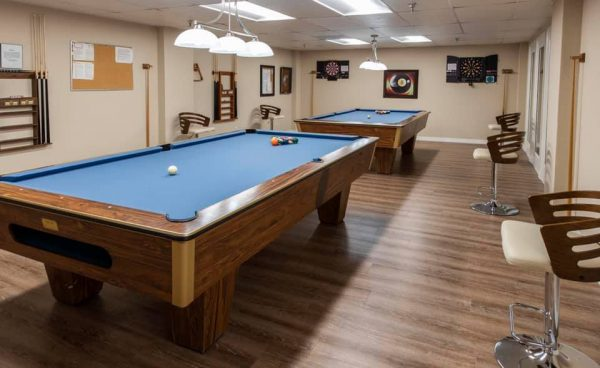 Blue felt covered pool tables in the Freedom Plaza Care Center billiards room
