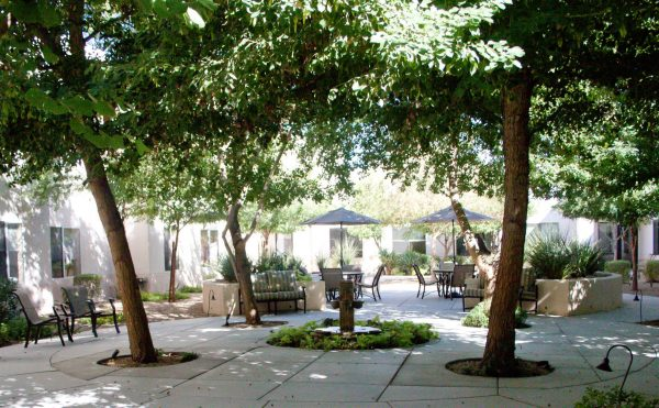 The Inn at Freedom Plaza outdoor courtyard filled with shade trees and umbrella tables