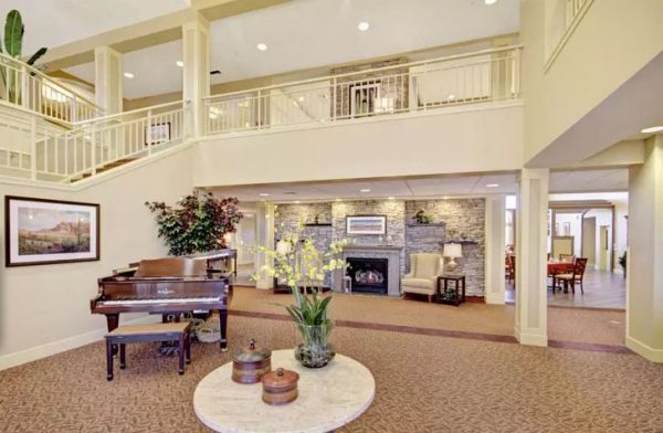 Lobby area with a grand piano and 2 story balcony in The Oaks, a Merrill Gardens community