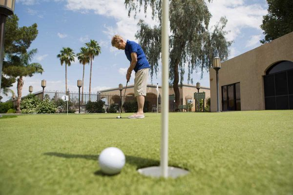 Senior woman playing golf on the putting green at Sierra Winds
