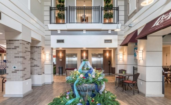Lobby and resident area with water fountain and balcony at American House Wyoming