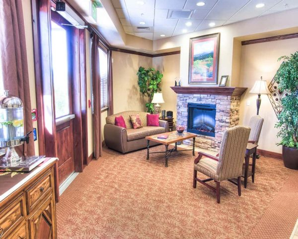 Community living room and fireplace in Canyon Valley Memory Care