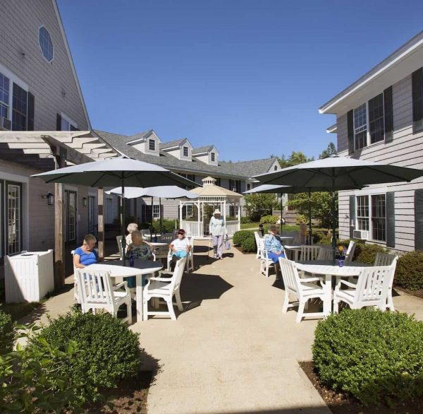 Outdoor dining tables on the Cape Cod Senior Residences patio
