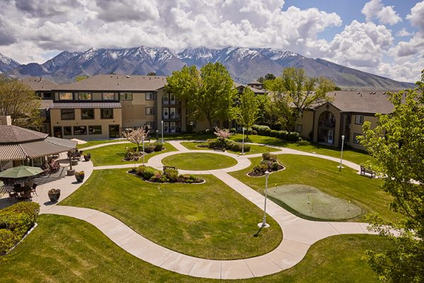 The grounds of Cedarwood at Sandy with mountains behind the building
