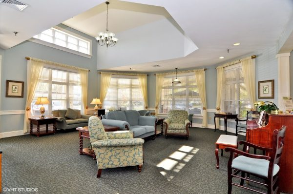 The piano room with comfortable seating and large windows at The Chesapeake Place