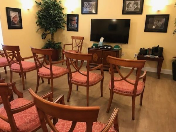 Crossings at Heritage community living room with many chairs facing a flat screen tv