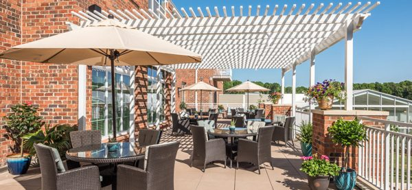Trellis covered deck with resident seating tables at Windsor Run