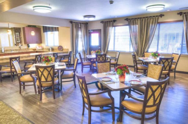 Community dining room with four top tables in Catalina Springs Memory Care