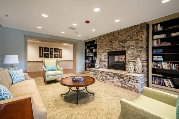 Discovery Village At Sugarloaf community living area with large stone fireplace and comfortable seating