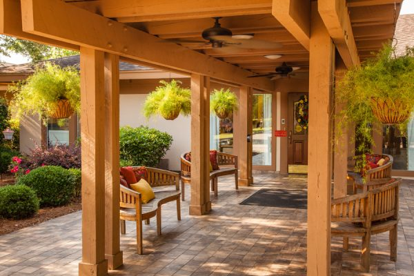 Covered walkway and resident seating outside of The Brennity at Fairhope