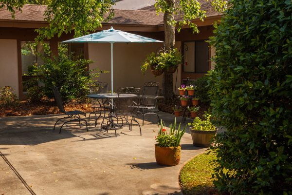 Umbrella table surrounded by plants and bushes on the The Brennity at Fairhope courtyard