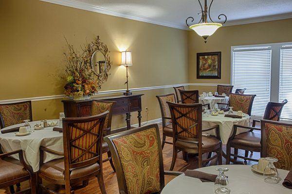 The Brennity at Fairhope community dining room with 4 top tables and chairs
