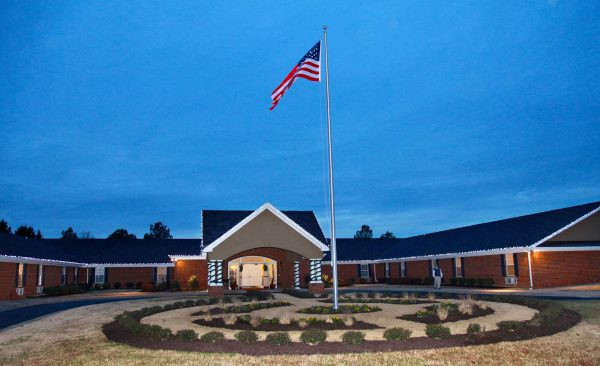 Front of building with American flag pole at Commonwealth Senior Living at Chesterfield at twilight
