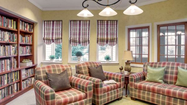 Atria Greenridge Place resident library with plaid stuffed chairs and bookcases