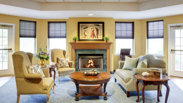 Resident community living room and fireplace in Atria Greenridge Place