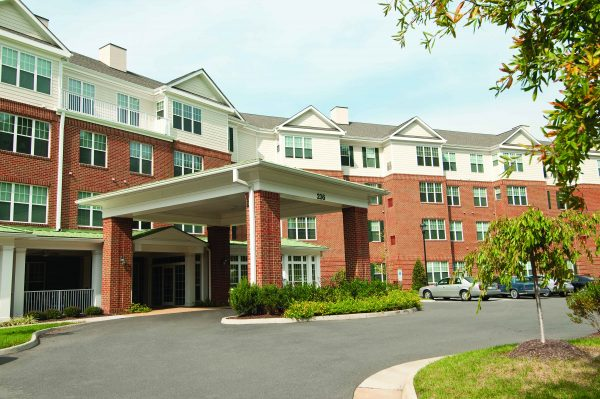 Commonwealth Senior Living at Williamsburg exterior view with brick fascia and covered entrance from driveway