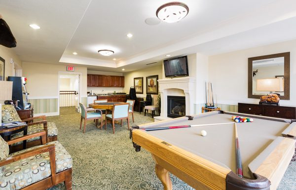 Game room in Palos Verdes Senior Living with a tan felt pool table, fireplace and card tables