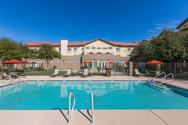 Mountain Park Senior Living outdoor swimming pool with lounge chairs and umbrella tables