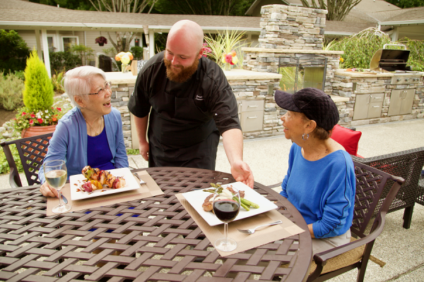 Aegis Living Issaquah chef preseenting senior women with gourmet meal at outdoor dining area
