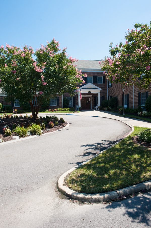 Winding driveway lined by trees to the entrance at Commonwealth Senior Living at King's Grant House