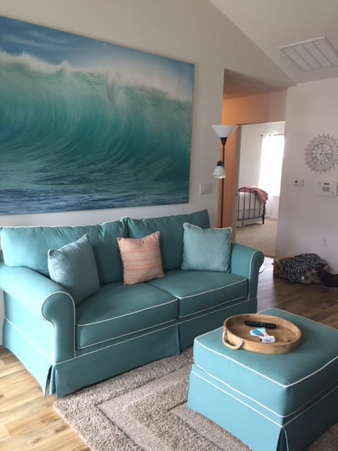 Big comfy aqua colored sofa with painting behind in residence at Crossings at Heritage