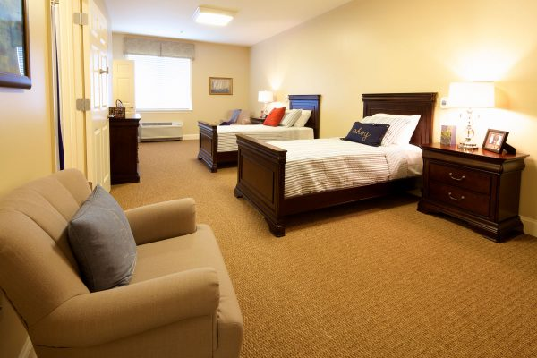 Model room with two single beds and seating at Commonwealth Memory Care at Chesapeake