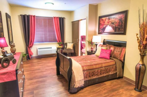 Model bedroom with a sleigh bed in Catalina Springs Memory Care