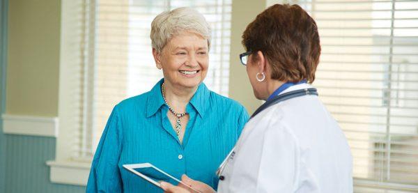 Senior woman smiling at female doctor