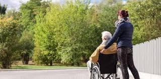 Woman pushing man in wheelchair outside of PruittHealth - Town Center with trees in the background