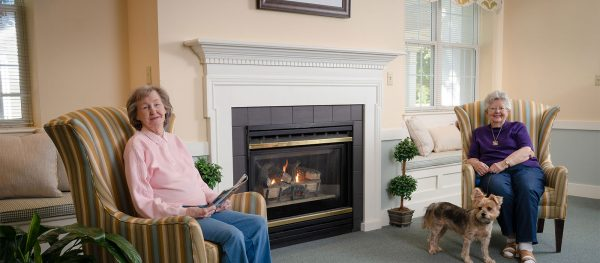 Residents of Mennowood Retirement Community reading by the fireplace