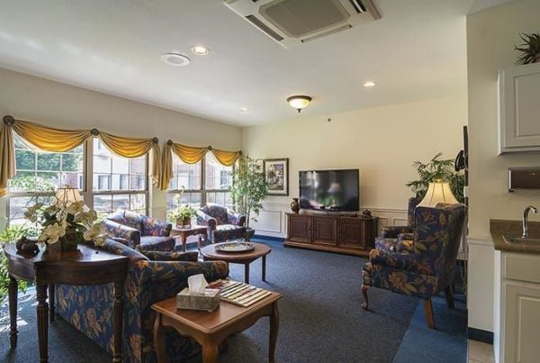 Community living room at Rittenhouse Village At Michigan City with seating for residents