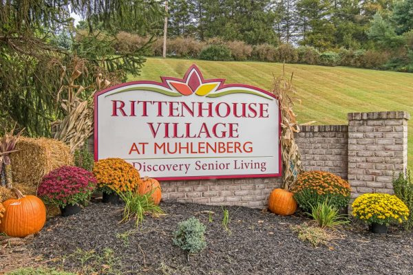Rittenhouse Village At Muhlenberg sign on brick wall at entrance surrounded by fall colored flowers and pumpkin