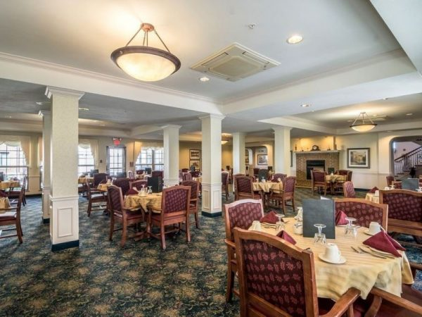Large dining room with comfortable arm chairs for residents of Rittenhouse Village At Portage