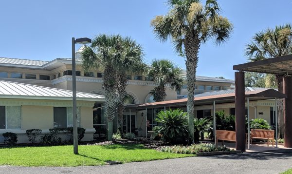 Front entrance on a sunny day at Savannah Grand of Amelia Island with long covered walkway and large palm trees in front