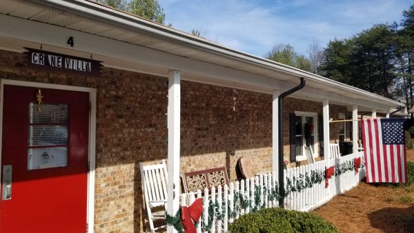 Shuler Health Care Assisted Living entrance to brick front building with rocking chairs under porch