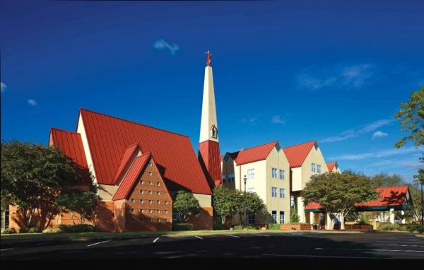 Exterior view of St. Catherine's Village with soaring steeple, lush landscape and deep blue sky
