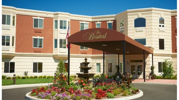 The Bristal Assisted Living at East Northport main entrance with large dark brown awning covering driveway with water fountain and colorful flowers in the rotunda