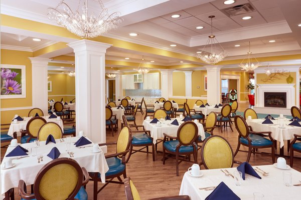 Main dining room with yellow and blue arm chairs and white pillars and coffered ceiling at The Bristal Assisted Living at Englewood