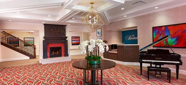 The Bristal Assisted Living at Garden City lobby with reception desk, fireplace and coffered ceiling