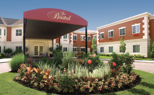 Gardens of flowers in front of the covered awning over the driveway entrance to The Bristal Assisted Living at Massapequa