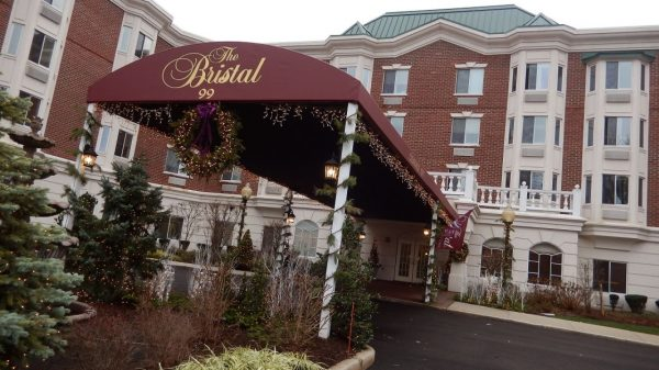 Maroon awning covering the driveway and entrance to The Bristal Assisted Living at North Hills