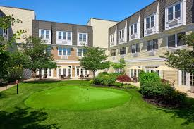 The Bristal Assisted Living at North Woodmere rear cortyard with lush green lawn and manicured hedges