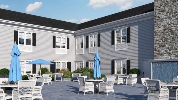 The Bristal Assisted Living at Somerset outdoor patio with white tables with blue umbrellas and the main building with black shutters in the background