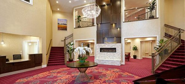 Lobby of The Bristal Assisted Living at Wayne with curved staircase and two story fireplace and red carpet